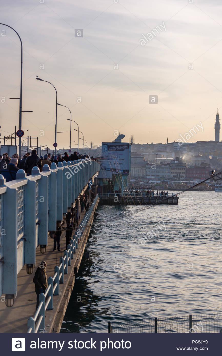 Fisherman fishing off Galata bridge along the Bosphorous in Istanbul, Turkey - Stock Image
