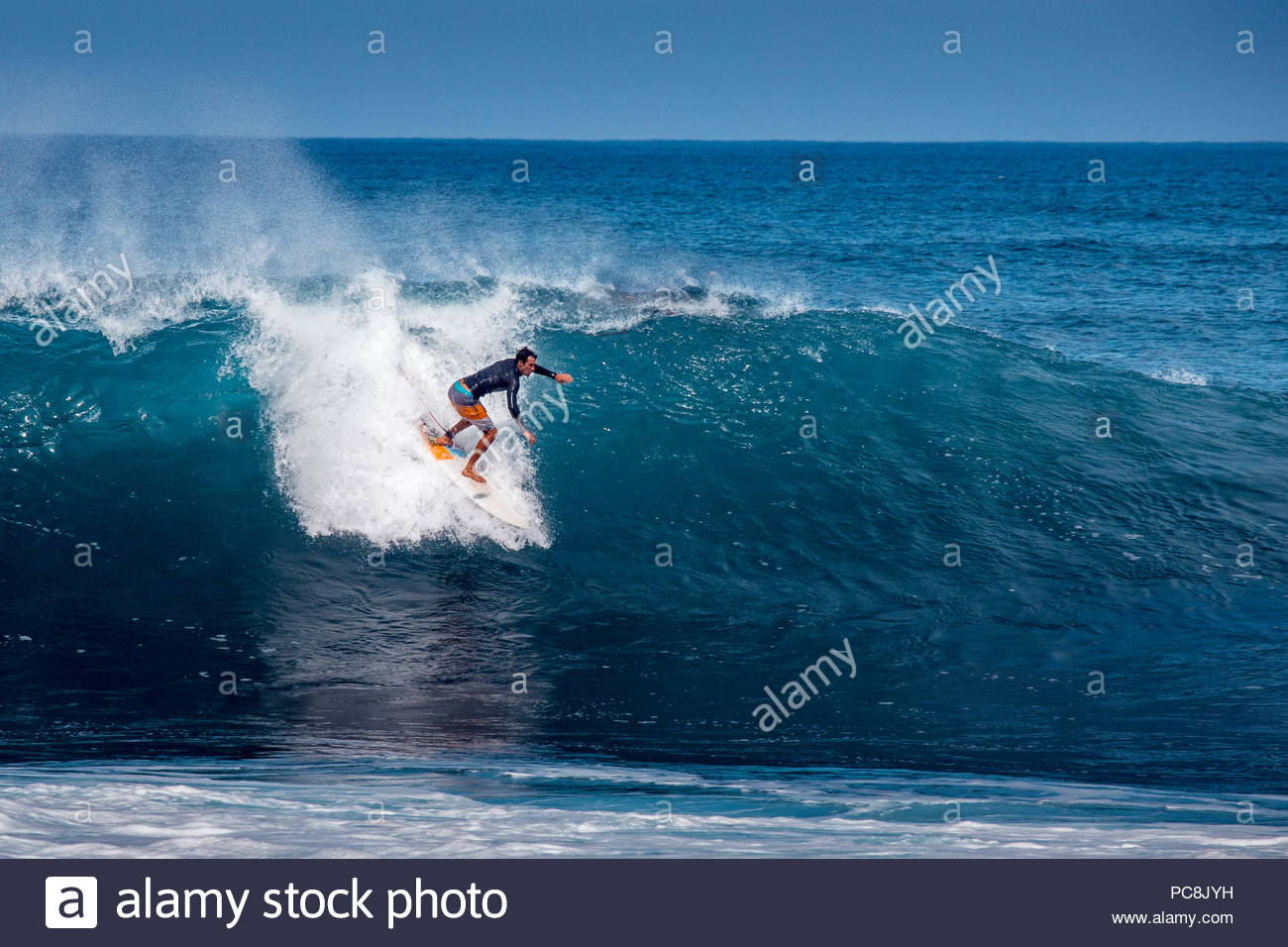 A surfer drops into a wave at Rocky Point. - Stock Image