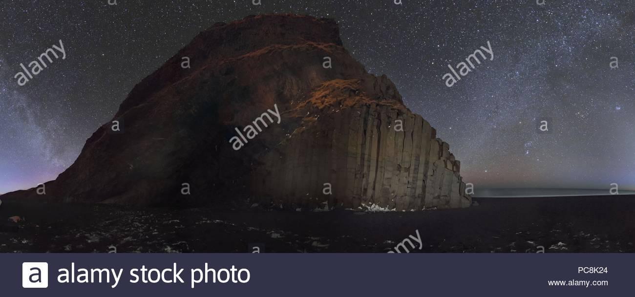 Starry sky and Winter Milky Way above basalt columns on the ocean coast. Stock Photo