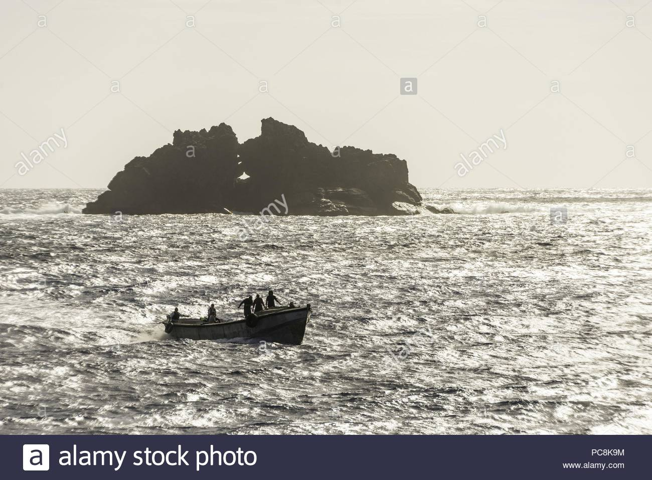 Island inhabitants use longboats to transport goods between the island and passing ships. - Stock Image