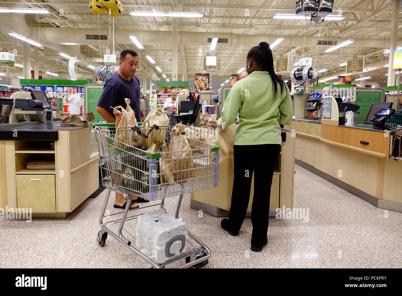 Florida Pompano Beach Publix grocery store supermarket food interior inside shopping checkout line queue cashier customer man Black woman employee - Stock Image