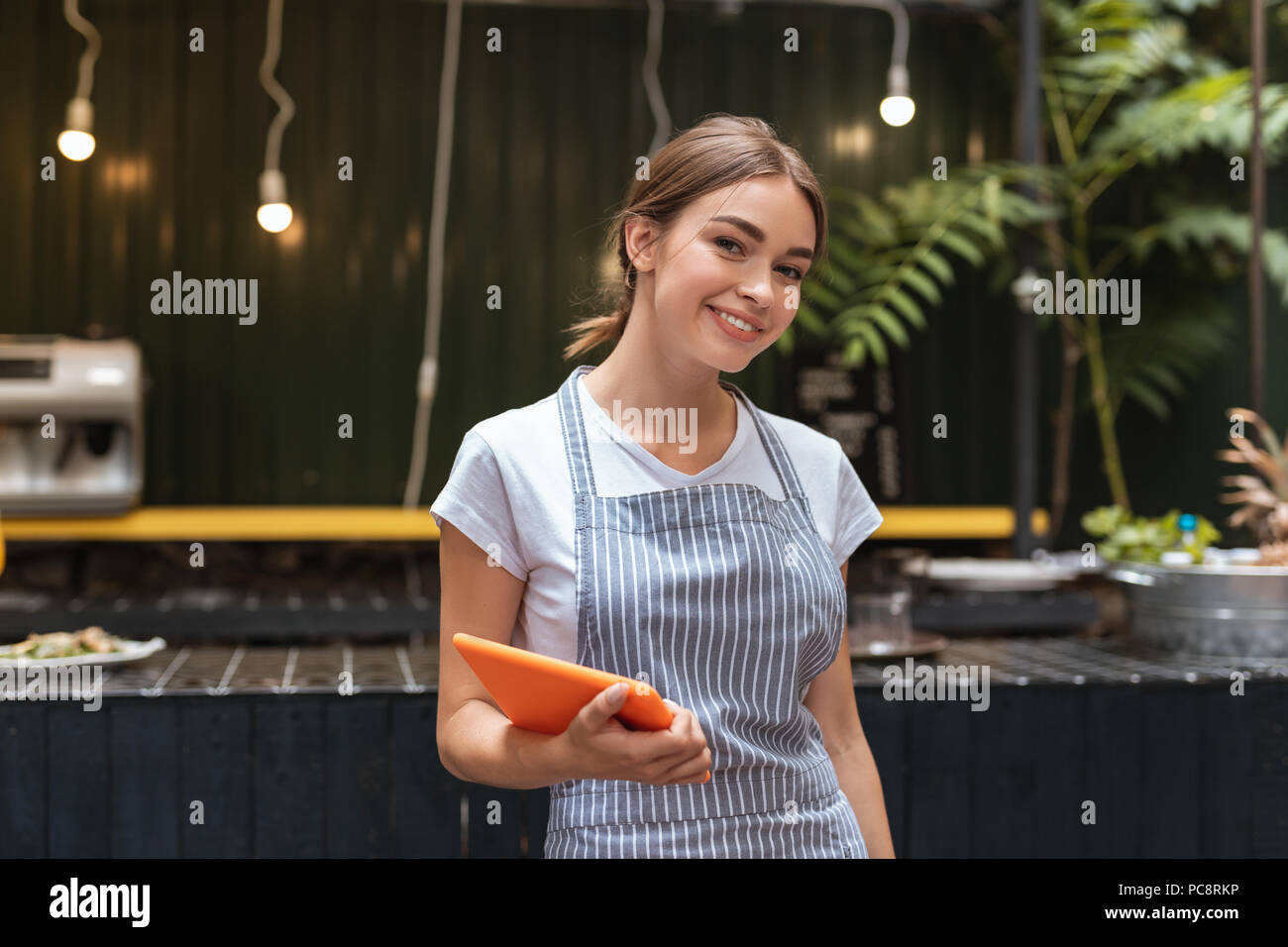 Beautiful waitress. Beautiful waitress wearing her uniform feeling good while welcoming guests of restaurant - Stock Image