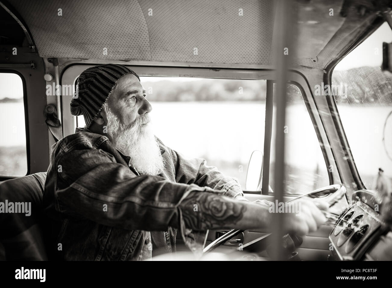 Senior hipster driving a van by countryside - Stock Image