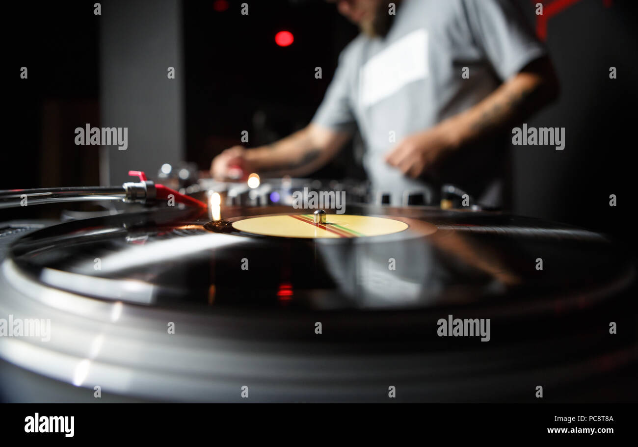 Professional dj turntable records player in close up. Disc jockey mixing music on background. Sound recording studio equipment - Stock Image