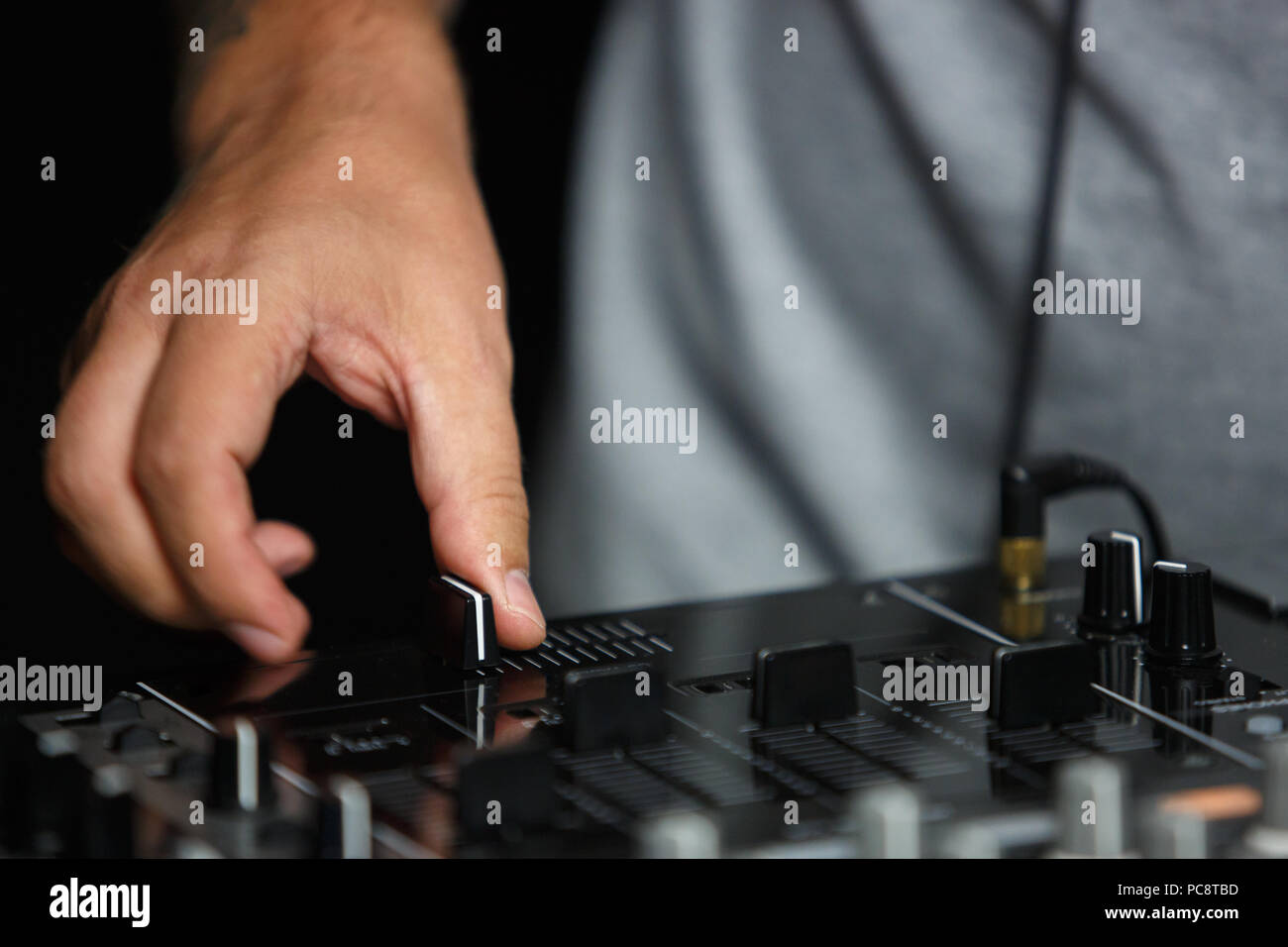 Hand of disc jockey adjusting the crossfader knob while palying live set on party in night club - Stock Image