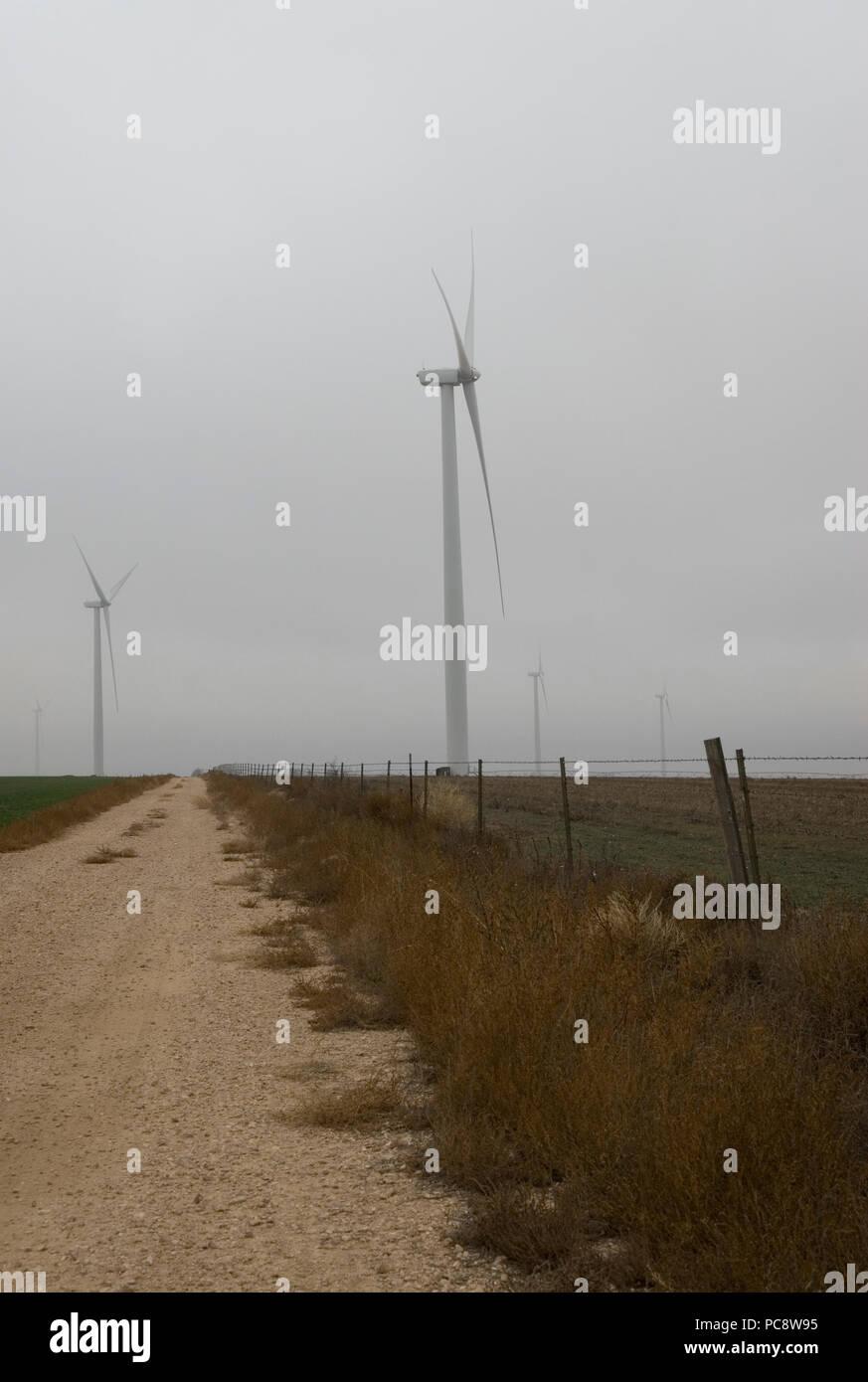 Giant windmills loom in fog near Groom, Texas USA - Stock Image