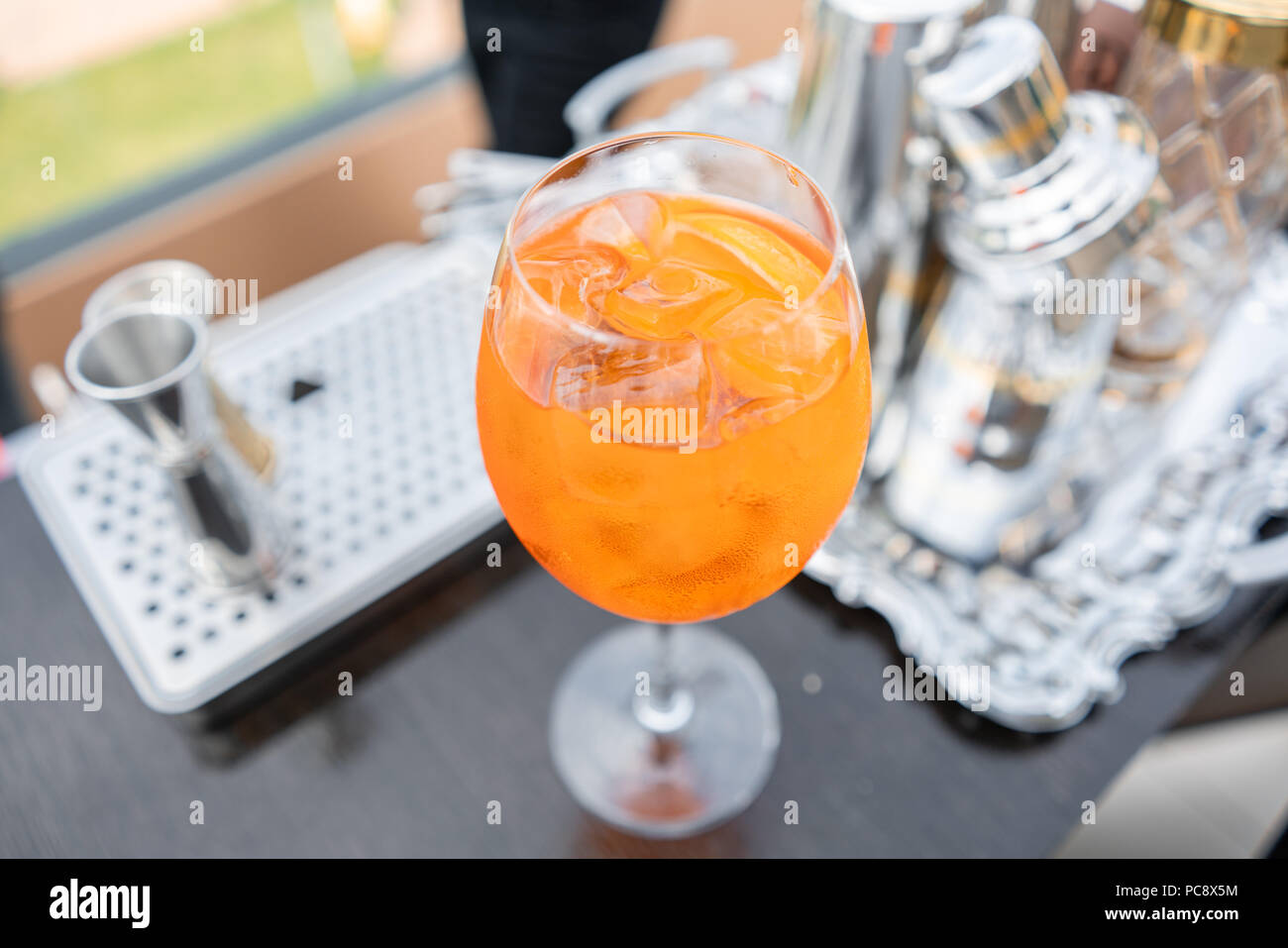 Aperol spritz cocktail in misted glass, selective focus. Alcoholic beverage based on bar counter with ice cubes and oranges. metal shakers in the background - Stock Image