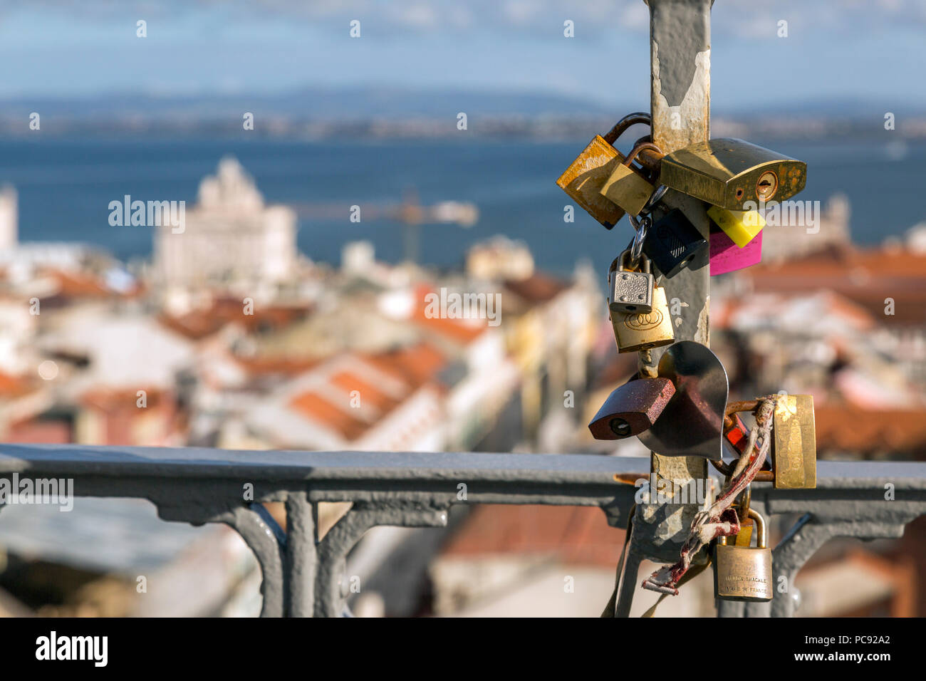 Love locks with city of Lisbon, Portugal beyond , taken on top of the Elevador Santa Justa. Stock Photo