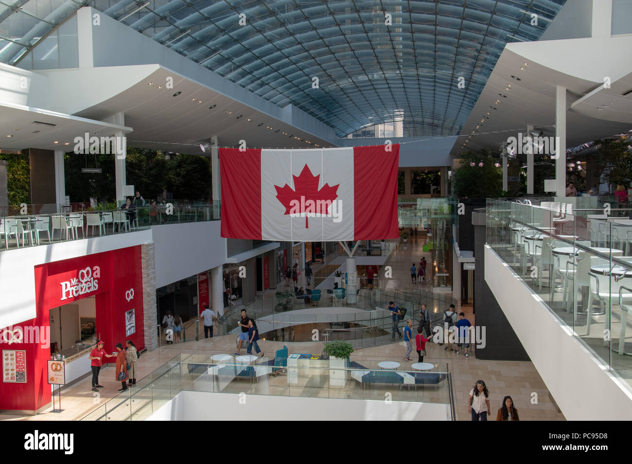 A giant Canadian flag spans the Core Shopping Centre, Downtown Calgary, Alberta, Canada. - Stock Image