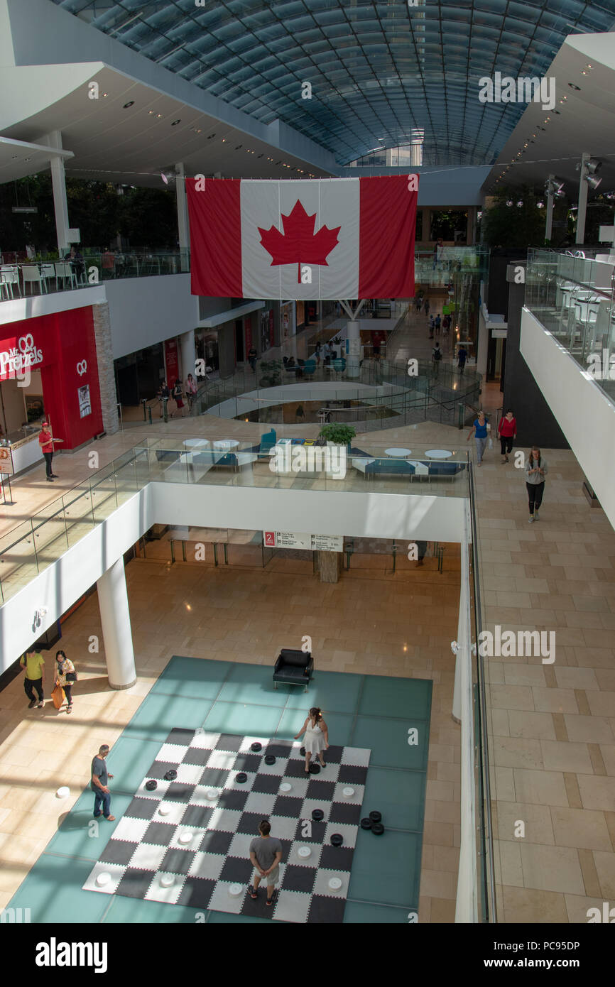 Shoppers play chess on the third level of the Core Shopping Centre, Downtown Calgary, Alberta, Canada. - Stock Image