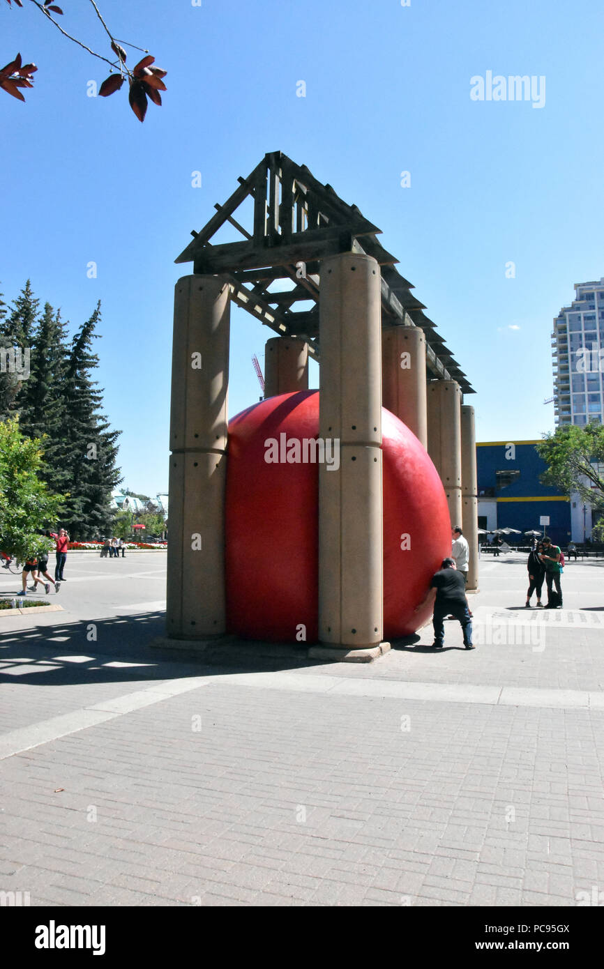 The Red Ball Project by artist Kurt Perschke wedged in the archs of Eau Claire Plaza in Calgary, Alberta, Canada - Stock Image