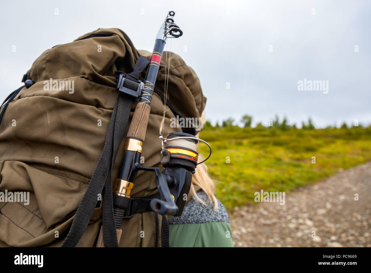 Close Up View Of Back Tourist Woman Brown Backpack And Fishing Rod Wearing On Green Tourism Jacket And Walking Along The Path To The Mountains On A Stock Photo Alamy