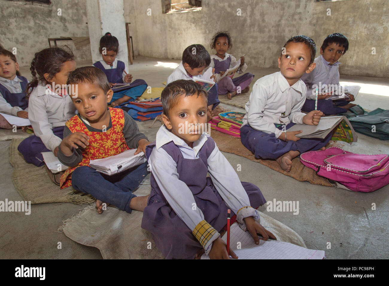 Indian Rural school kids learning from books in the classroom. - Stock Image