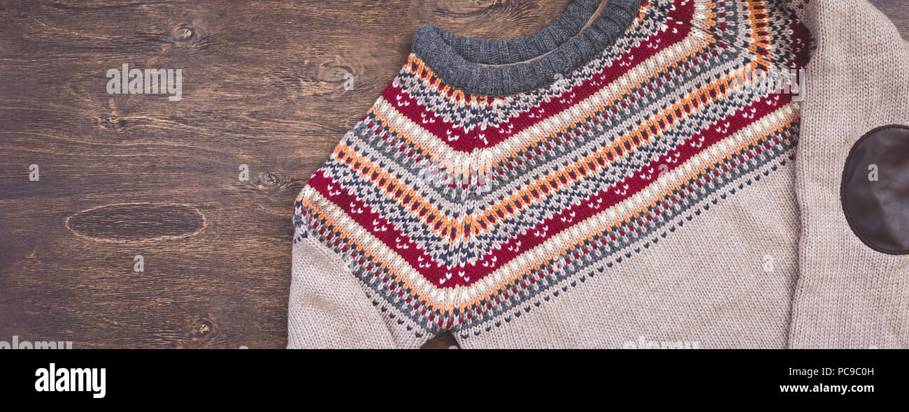 db30d6d2ceb902 Grey, orange, bordo and beige knitted sweater on wooden background - Stock  Image