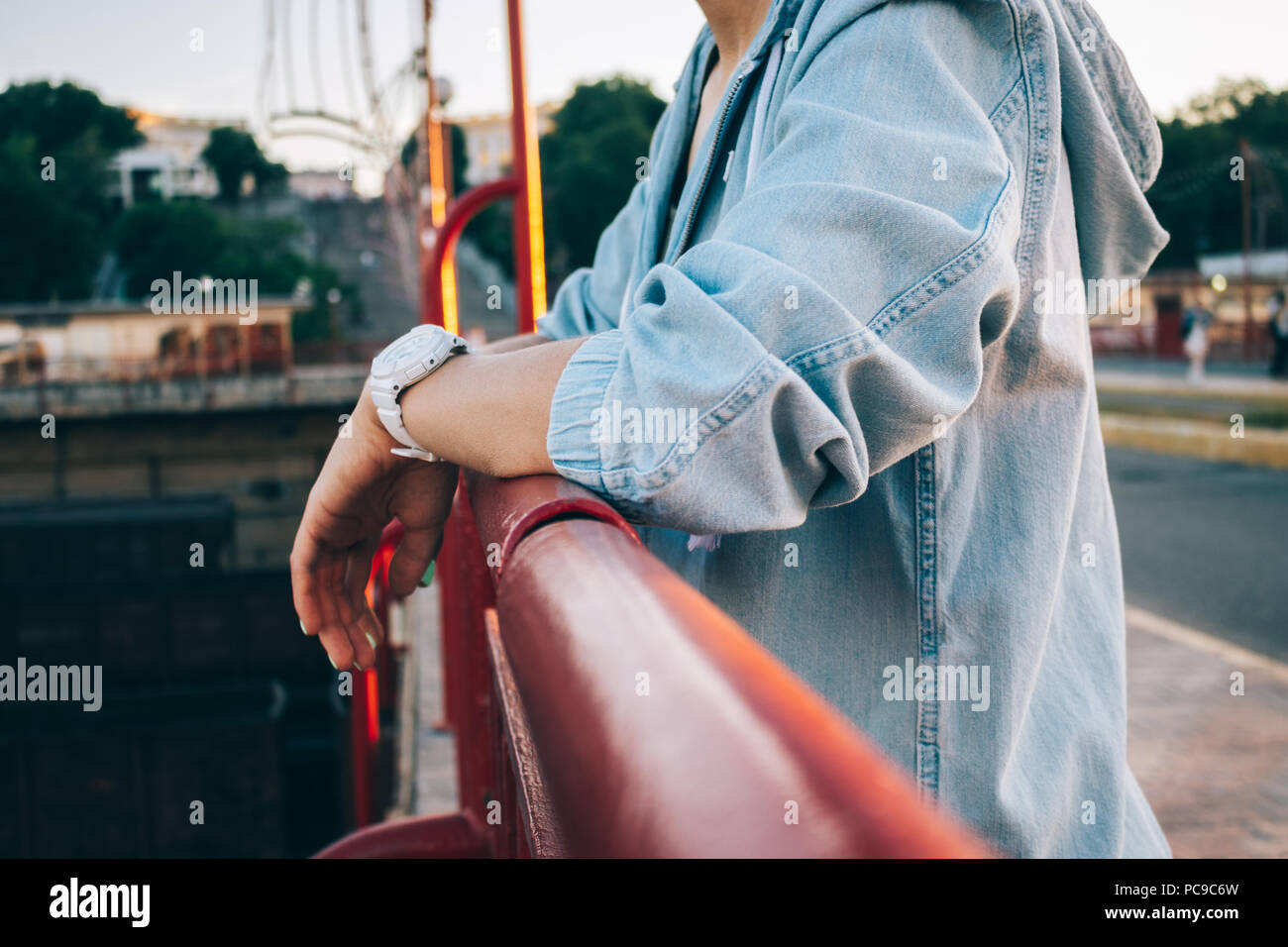Close-up young woman in jeans jacket standing next to bridge parapet. Candid lifestyle photo of female hands wearing wristwatches leaning on railing c - Stock Image