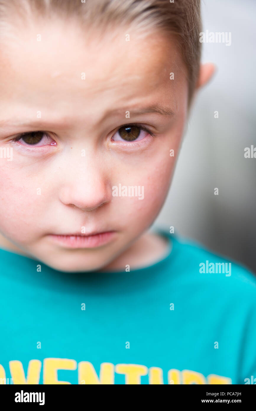 Closeup of teary eyed little boy - Stock Image