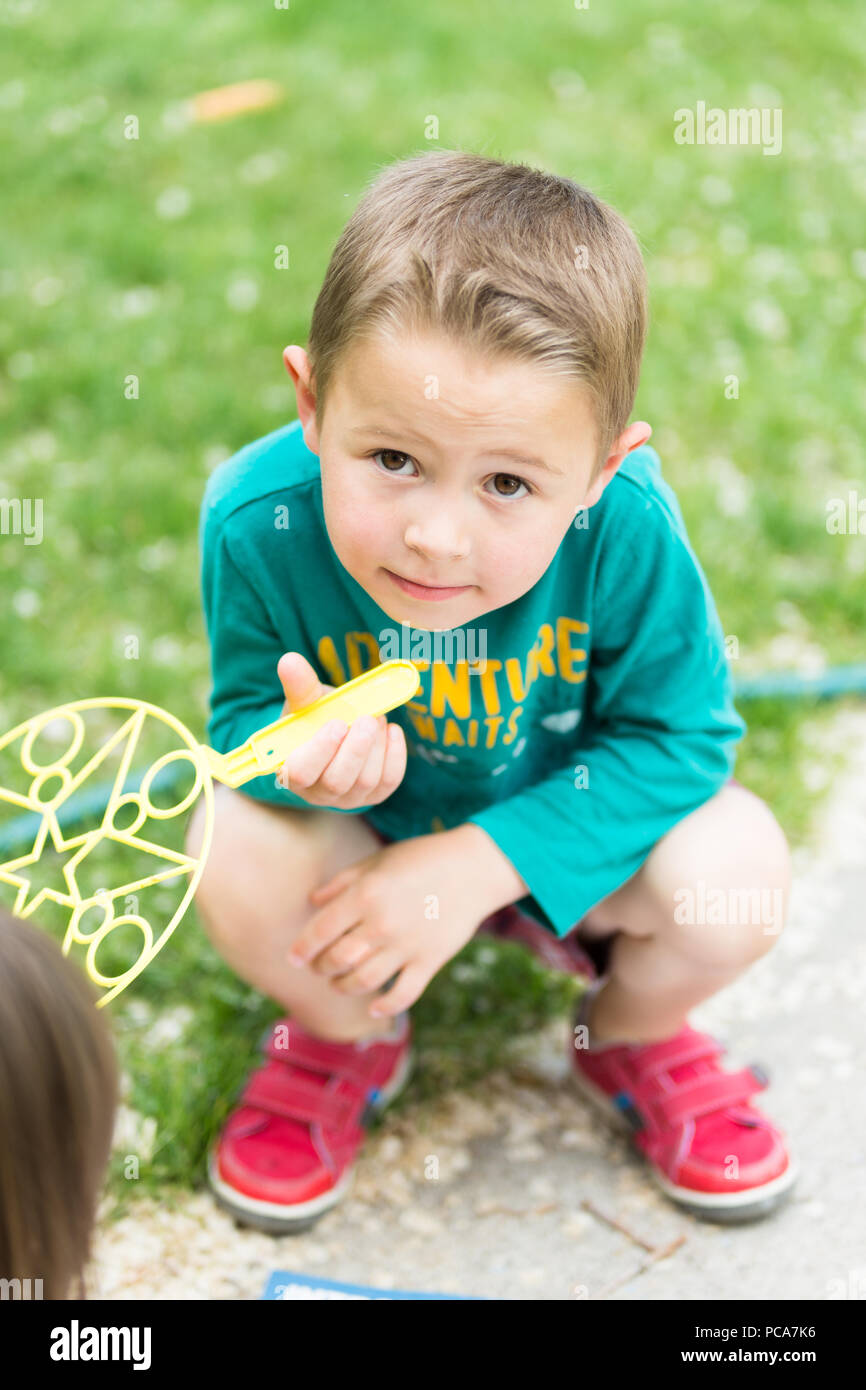 Boy squatting down in front yard to play - Stock Image