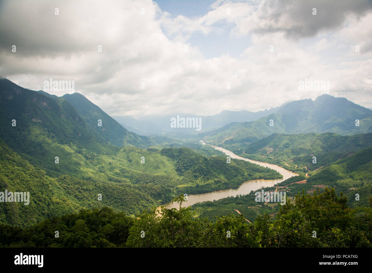 Nam Ou river flowing through beautiful lush green landscape seen from a viewpoint above Nong Khiaw in Laos PDR. - Stock Image