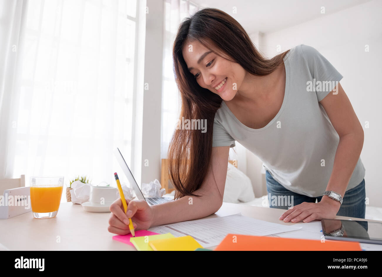 Asian female freelancer standing and writing on paperwork working on table in bedroom at home.Work at home concept.work from home concept - Stock Image