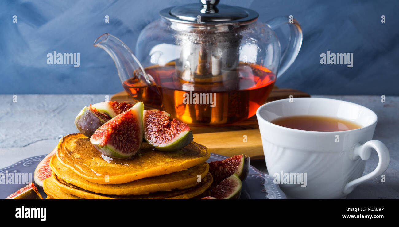 Stack of pumpkin pancakes with figs and honey and hot tea. Autumn food background on blue gray backdrop Stock Photo