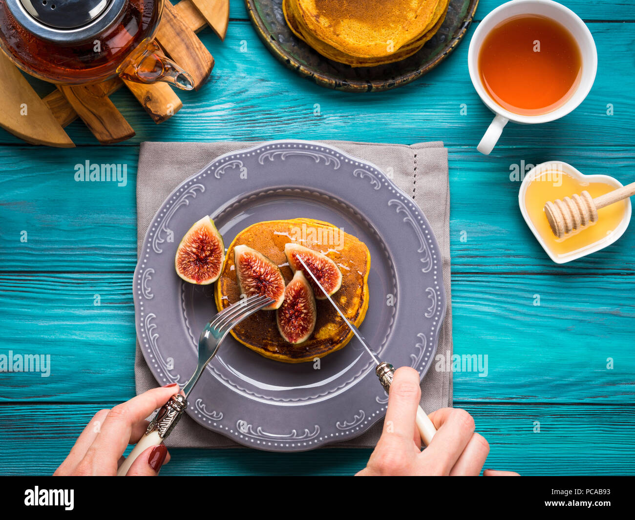 Eating pumpkin pancakes with figs and honey with hot tea. Autumn food background on green wooden table. Woman's hands Stock Photo