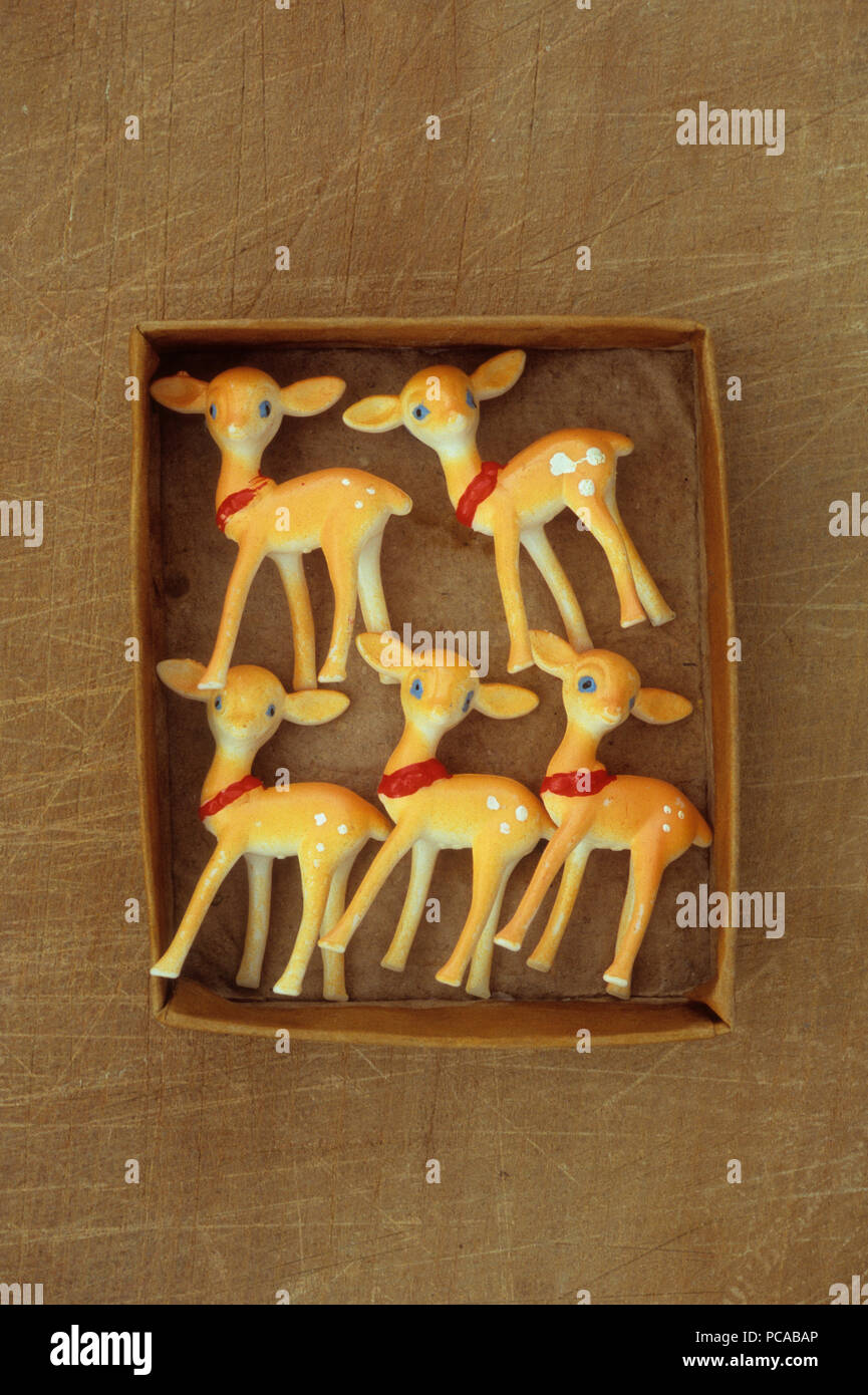 Five plastic models of fawn coloured young deer lying in cardboard box - Stock Image