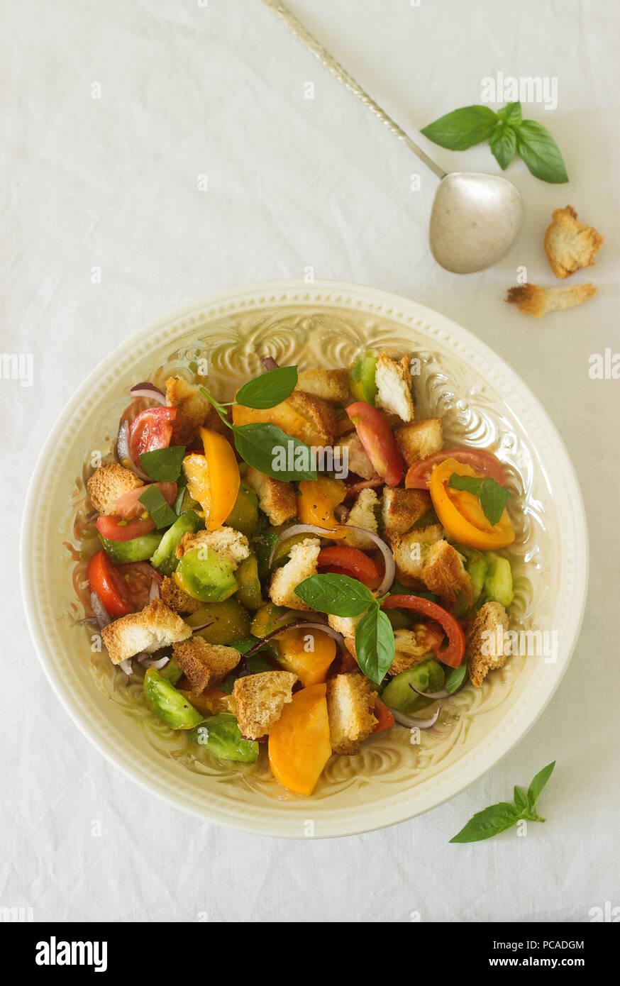 Salad of tomatoes and bread panzanella in a round plate on a light background. Rustic style. - Stock Image