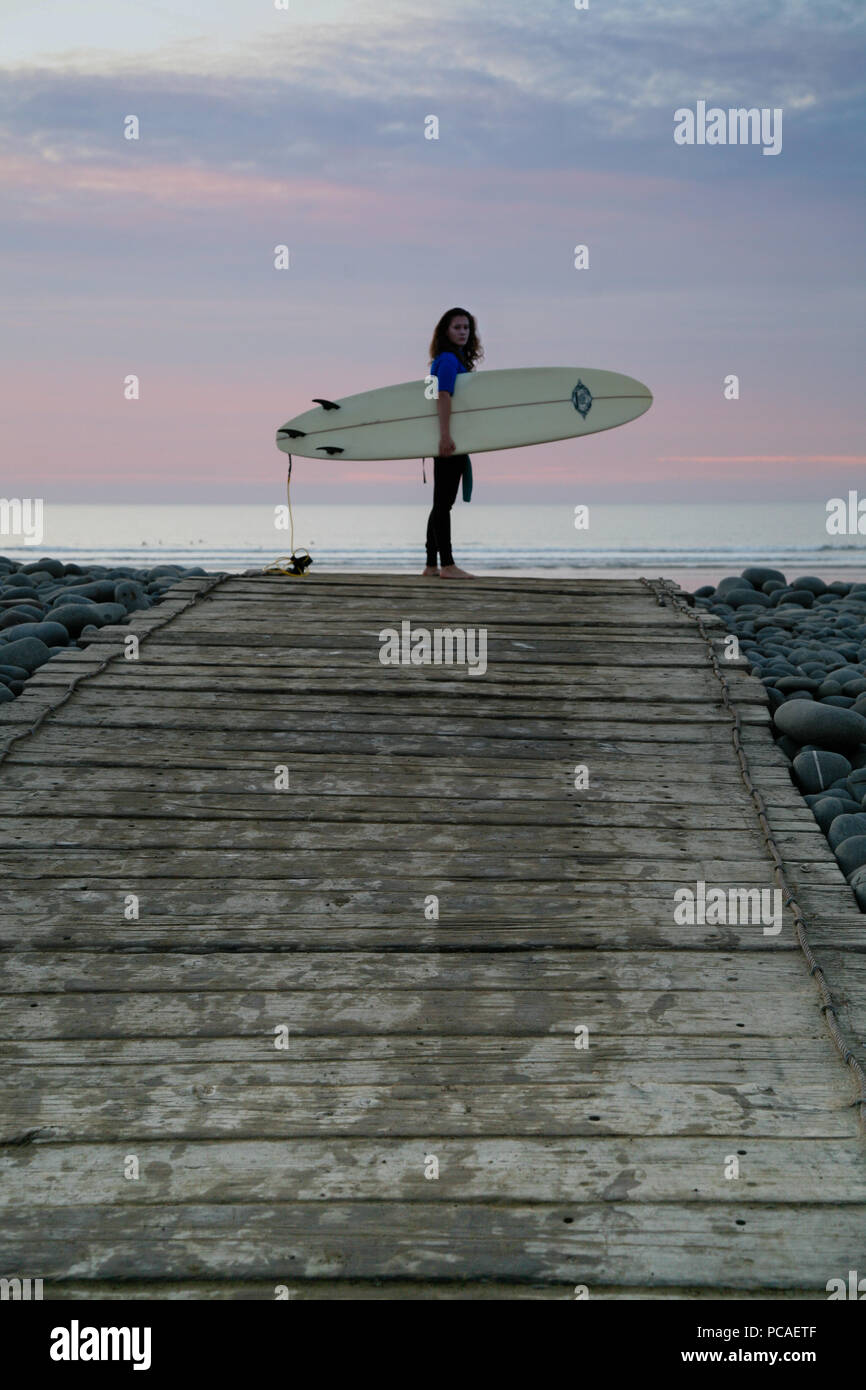 Female surfer standing on pebble ridge with surfboard before heading off into the sea to surf at Westward Ho! beach, North Devon, England, Europe. Stock Photo