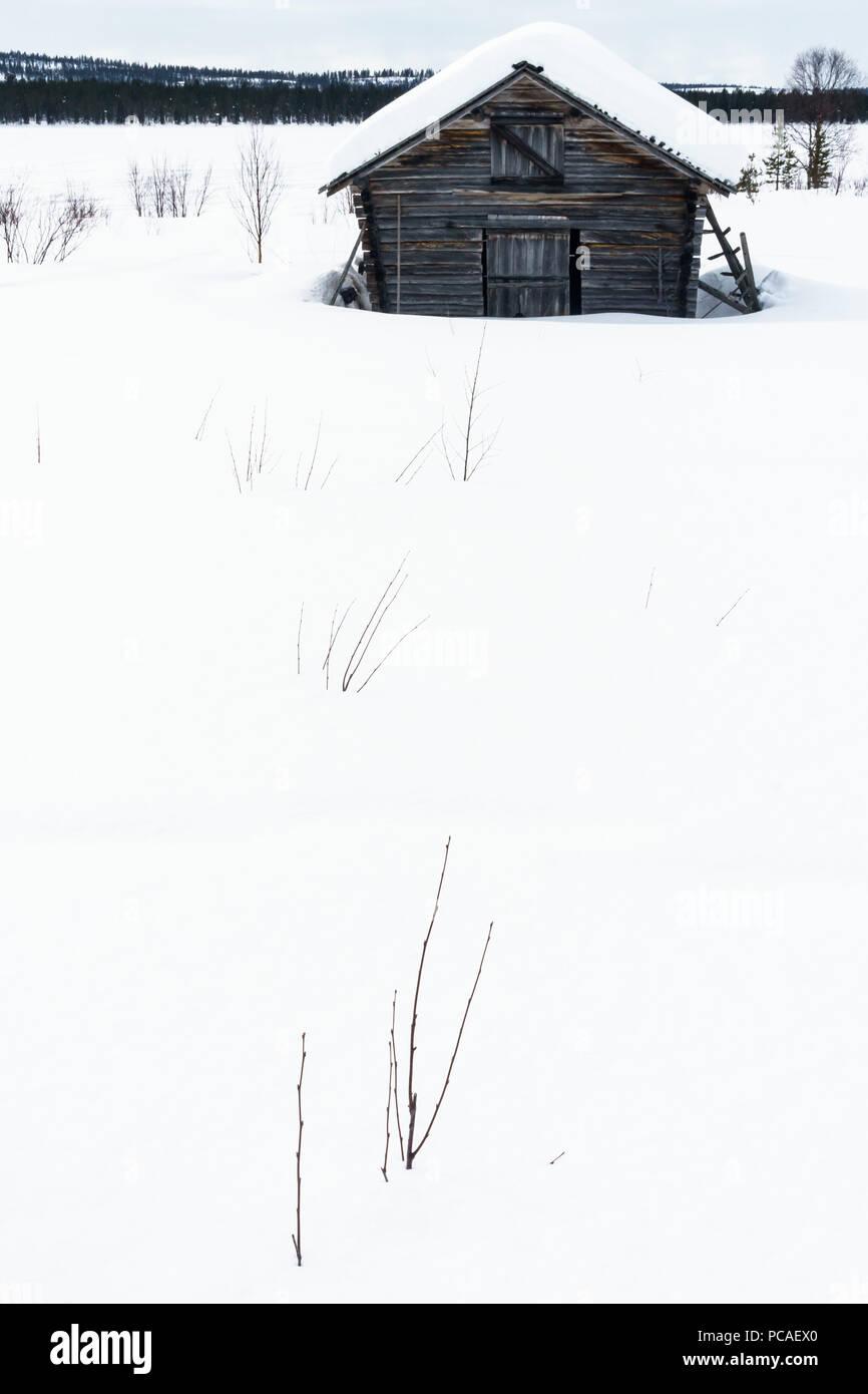 Clapboard barn buried in the snow in stark landscape, Torassieppi, Lapland, Northern Finland, Scandinavia, Europe - Stock Image