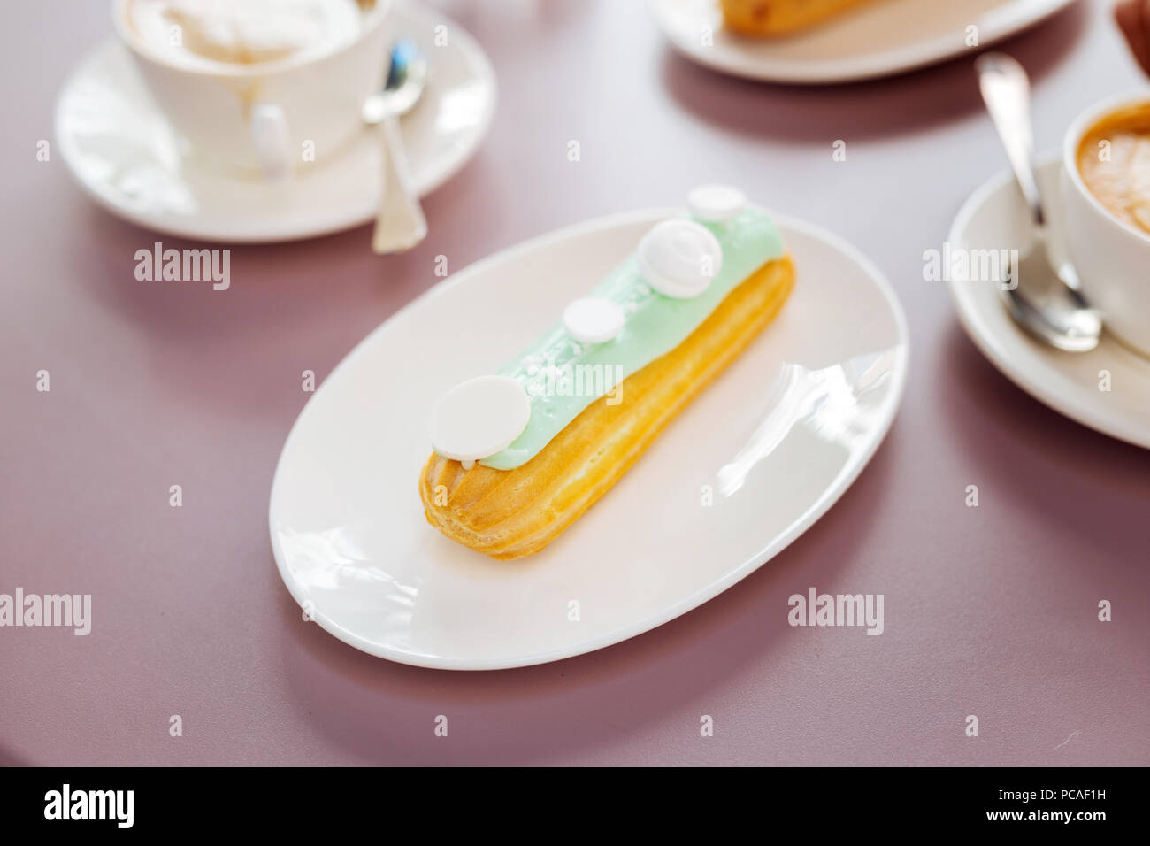 Amazing eclair resting on plate Stock Photo