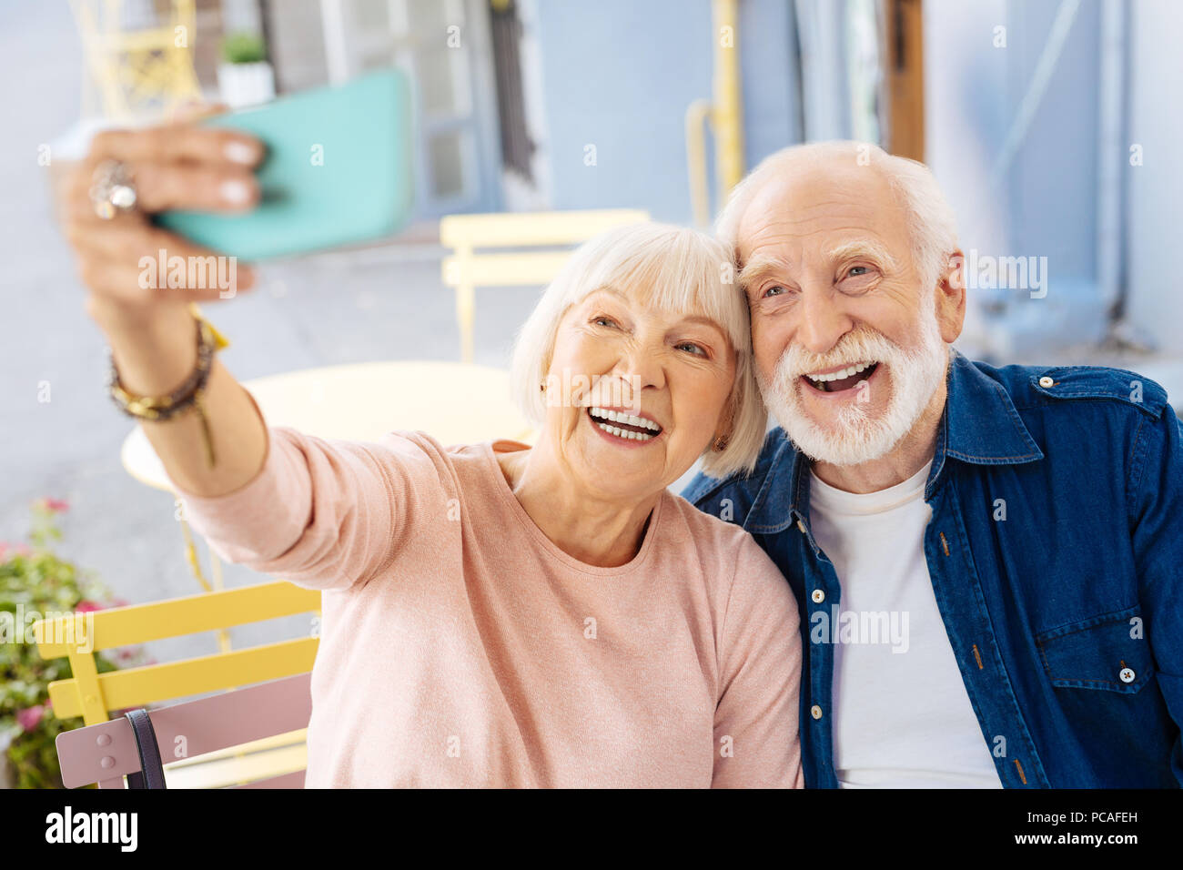 Positive senior couple taking selfie - Stock Image