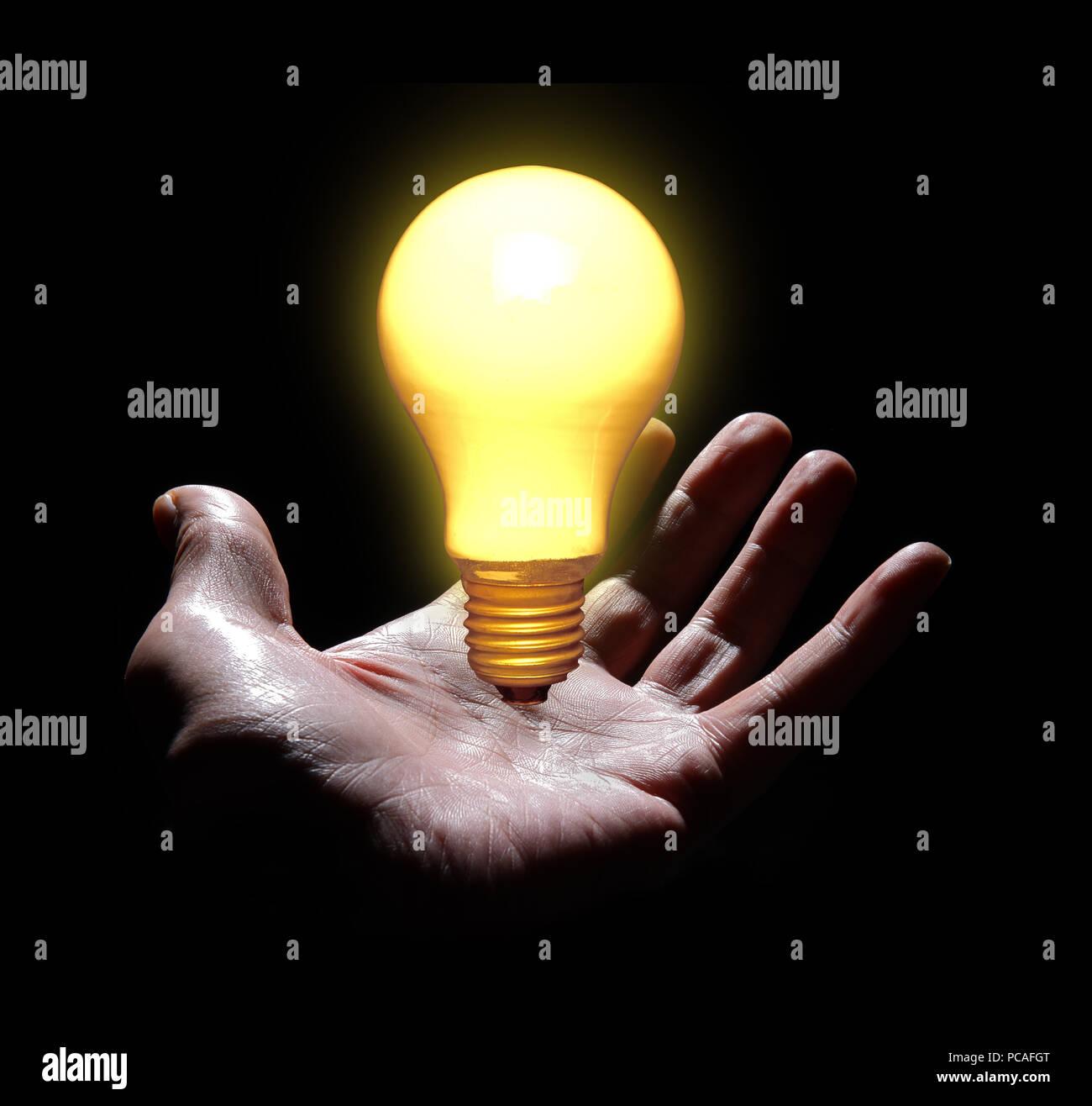 Hand and lightbulb. - Stock Image