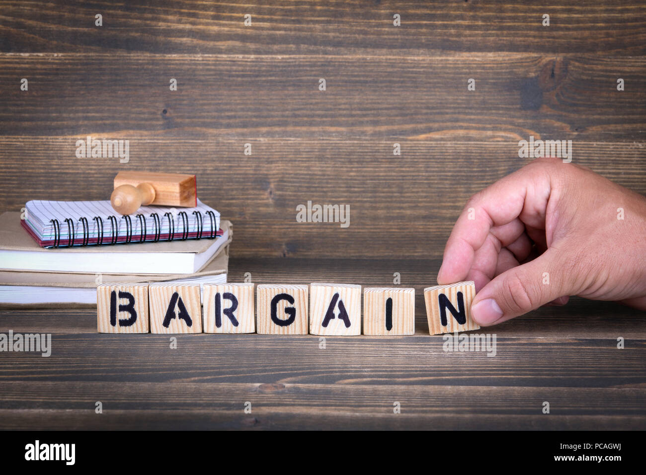 bargain. wooden letters on the office desk - Stock Image