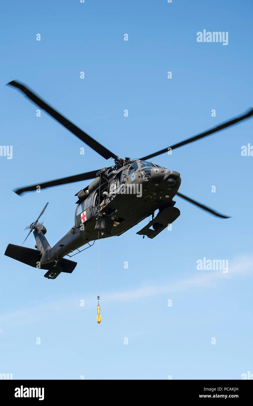 An Alaska Air National Guard UH-60 Black Hawk hovers above the landing zone during casualty evacuation training at Joint Base Elmendorf-Richardson, Alaska, July 19, 2018. Training was conducted by U.S. Marines with Delta Company, 4th Law Enforcement Battalion from Marine Corps Reserve Center, Billings, Montana. (U.S. Air Force photo by Airman 1st Class Caitlin Russell) - Stock Image