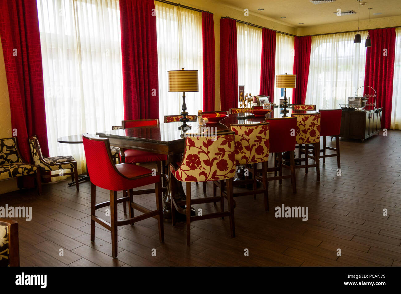 Formal dining room with red and white curtains and decor and seating for a large crowd of 12 persons Stock Photo