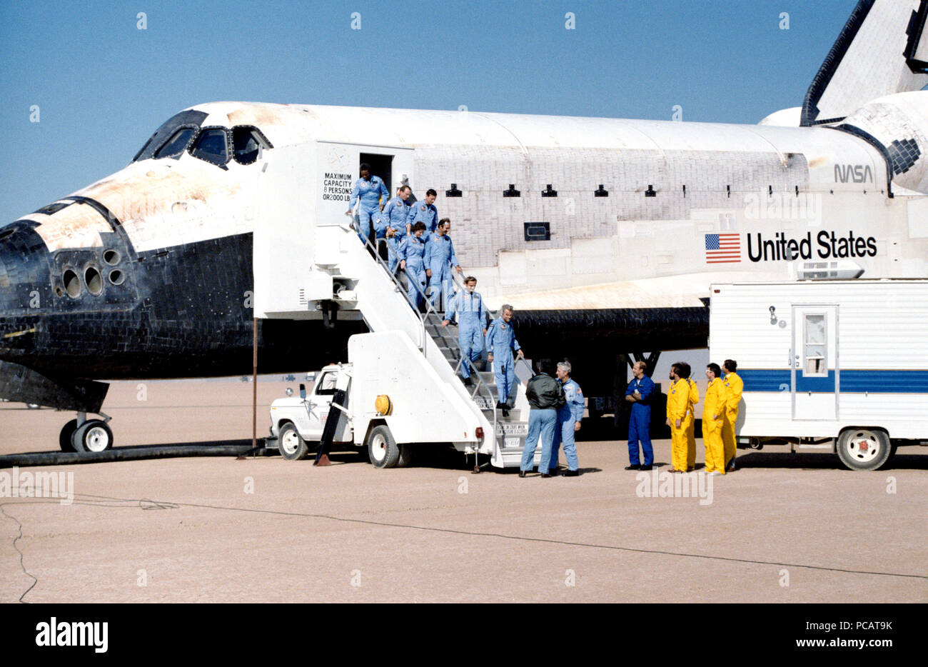 The crew of the STS 61-A mission egress the Orbiter after landing. Astronaut Henry W. Hartsfield Jr., 61-A mission commander, shakes hands with George W.S. Abbey, Director of Flight Crew Operations at JSC, as the rest of the crew descends the steps. From left to right are Guion S. Bluford, Jr., James F. Buchli, Steven R. Nagel, Bonnie J. Dunbar, Wubbo J. Ockels, Ernst Messerschmid, and Reinhard Furrer. November 6, 1985 - Stock Image