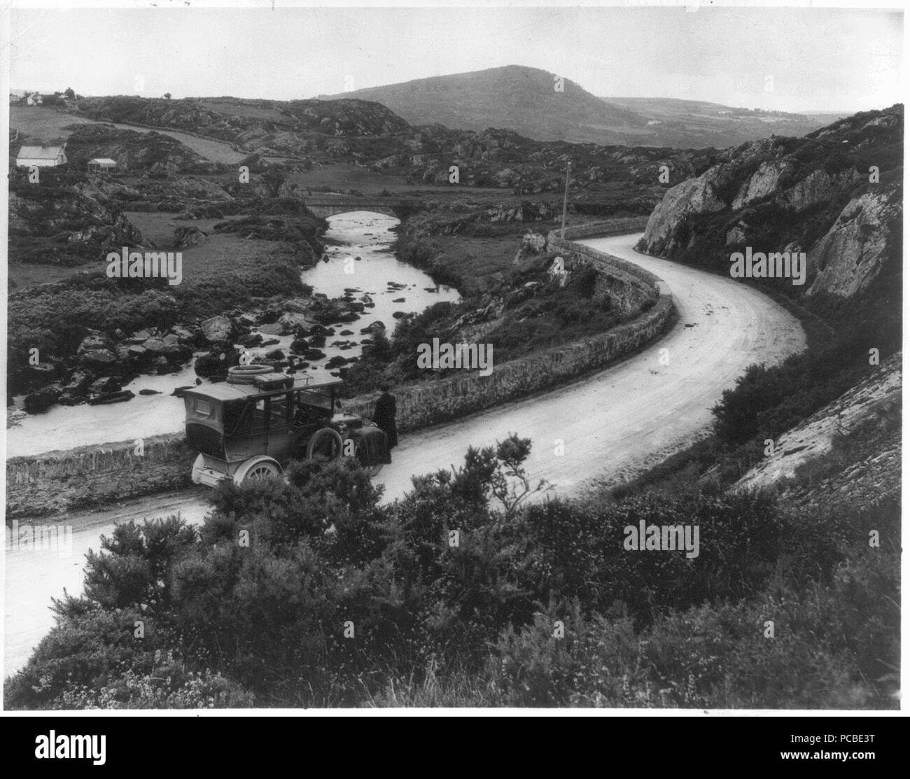 Auto parked on hillside road along stream. 1920-1930 - Stock Image