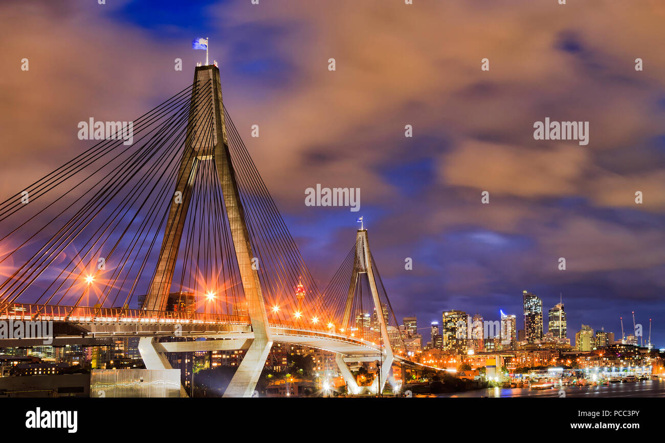 Modern urban bridge in Sydney city CBD against distant towers and cloudy  susnet sky with Australian anzac flag on tall column with lights and  illumina be317e03a5d4a