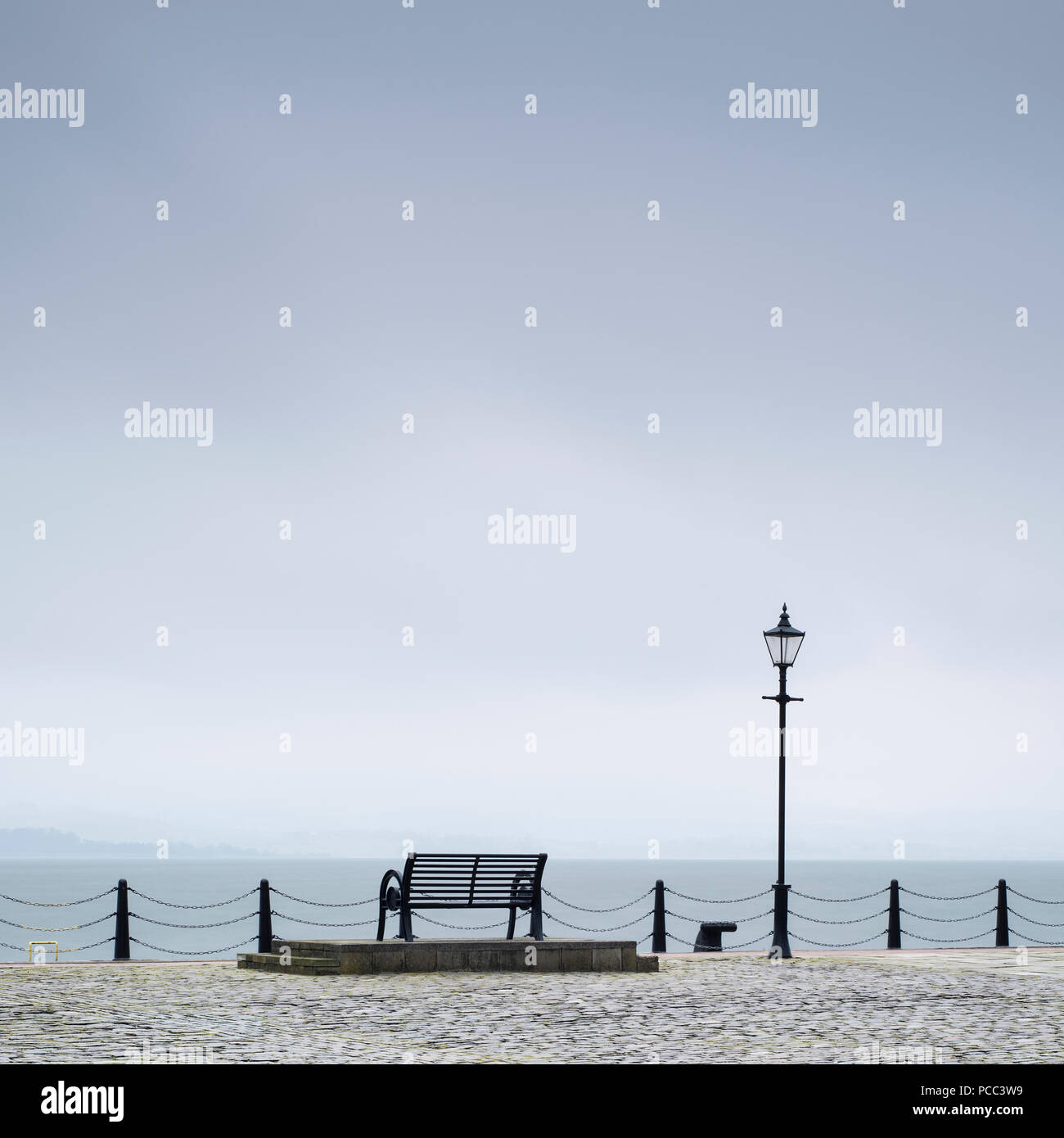 Lonely empty bench seat coastal sea peaceful quiet mindfulness scene view - Stock Image