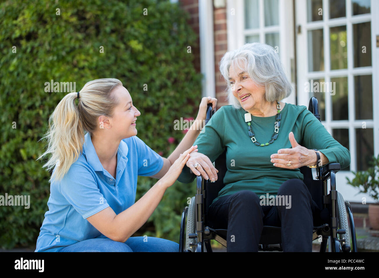 Carer Pushing Senior Woman In Wheelchair Outside Home - Stock Image