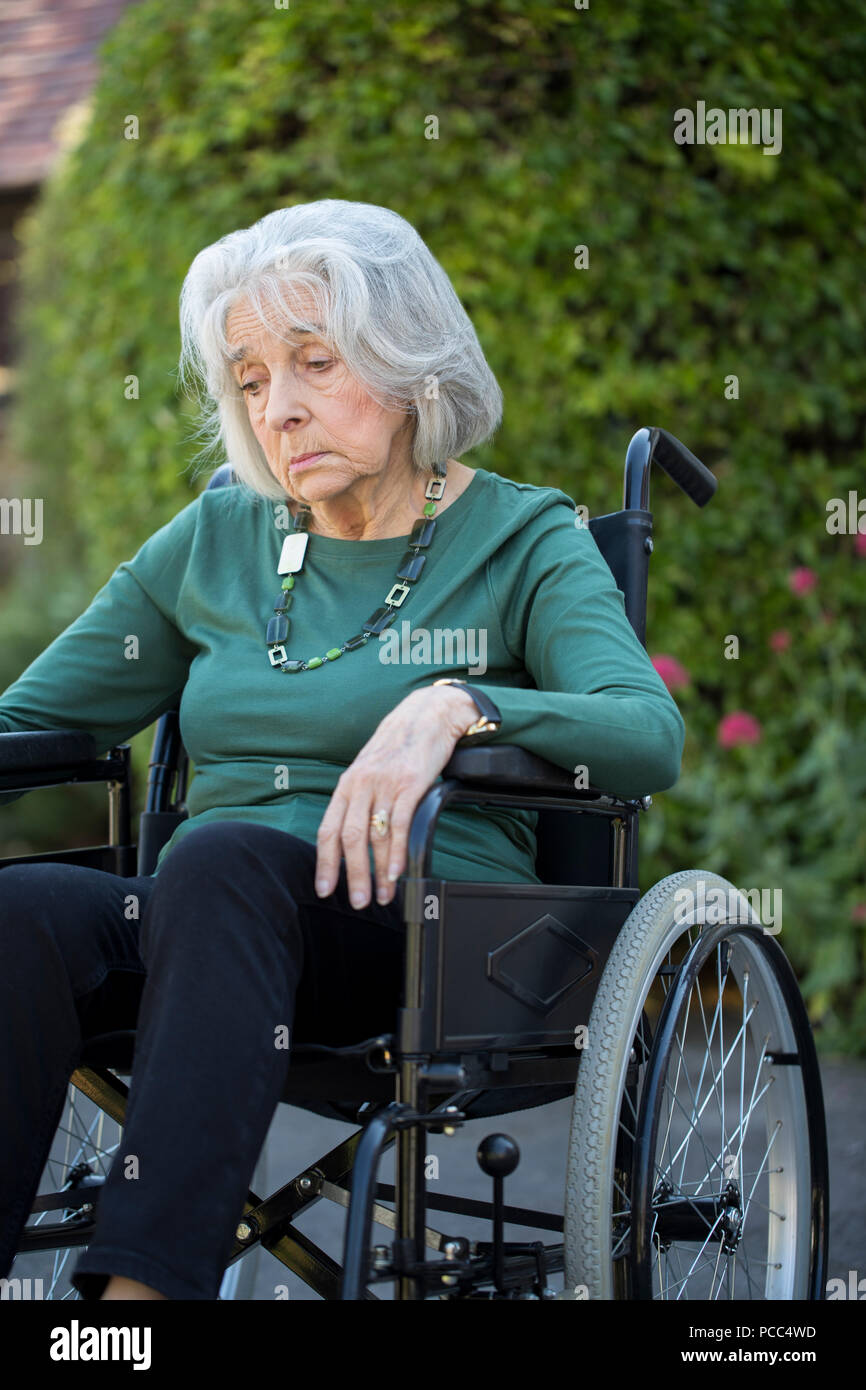 Depressed Senior Woman In Wheelchair Sitting Outdoors - Stock Image
