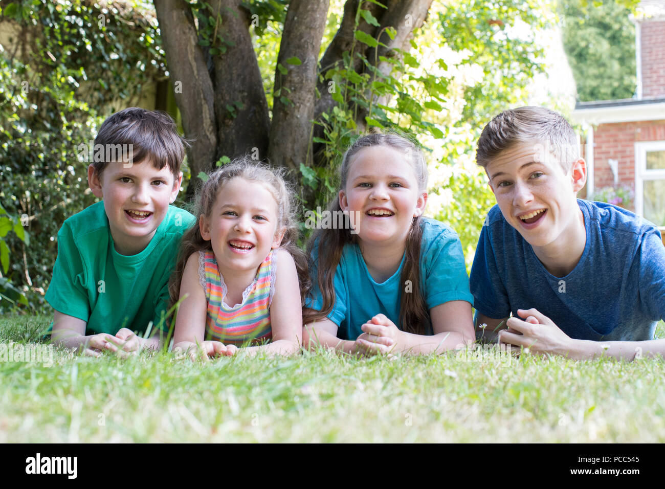 Portrait Of Four Brothers And Sisters Lying In Garden At Home - Stock Image