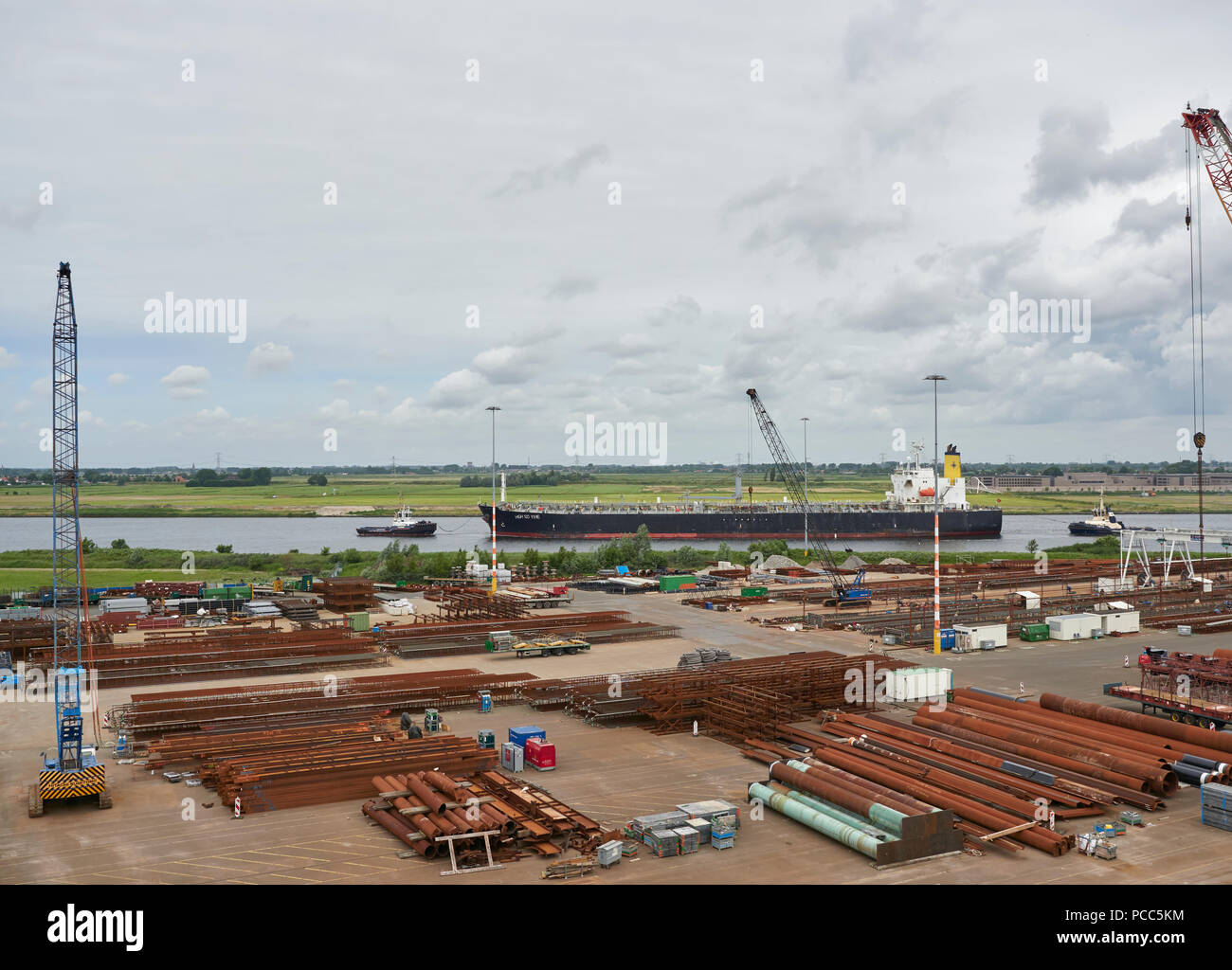 The High SD Yihe, a General Purpose Cargo Vessel being moved into the North Sea Canal by 2 Tugs at Den Haag, Amsterdam, Netherlands. - Stock Image