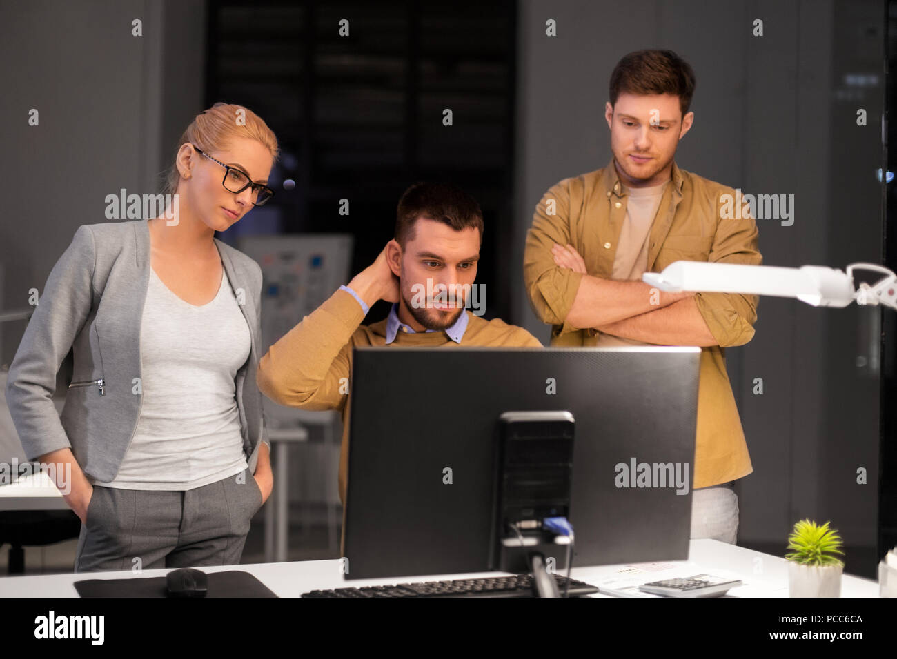 business team with computer working late at office - Stock Image