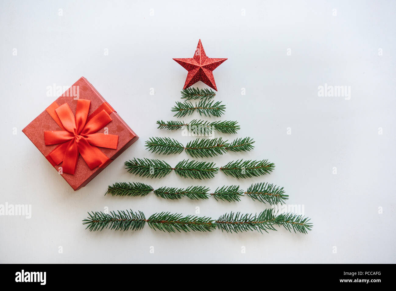 creative idea for christmas or new year theme a creative christmas or new year tree made of fir branches and a star on top there is a gift to the red box
