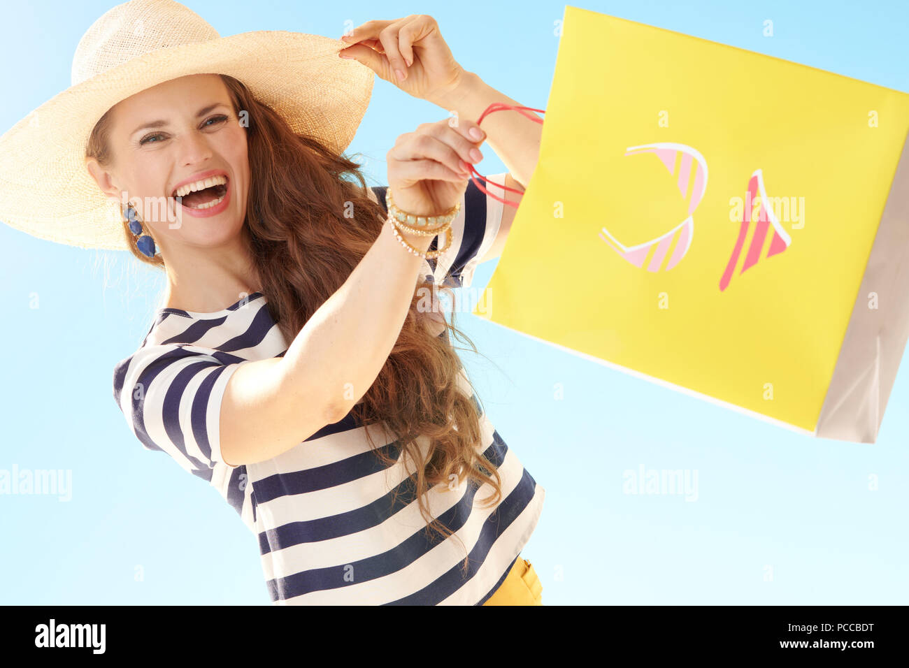 cheerful trendy woman in straw hat against blue sky with yellow shopping bag with bikini - Stock Image