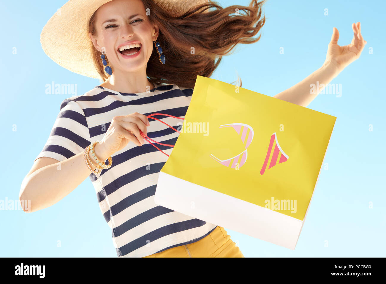cheerful modern woman in straw hat against blue sky with yellow shopping bag with bikini - Stock Image
