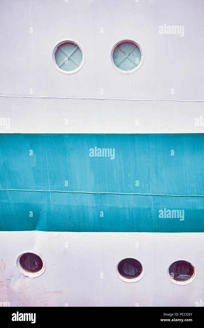 Retro toned close up picture of an old ship side with portholes. - Stock Image