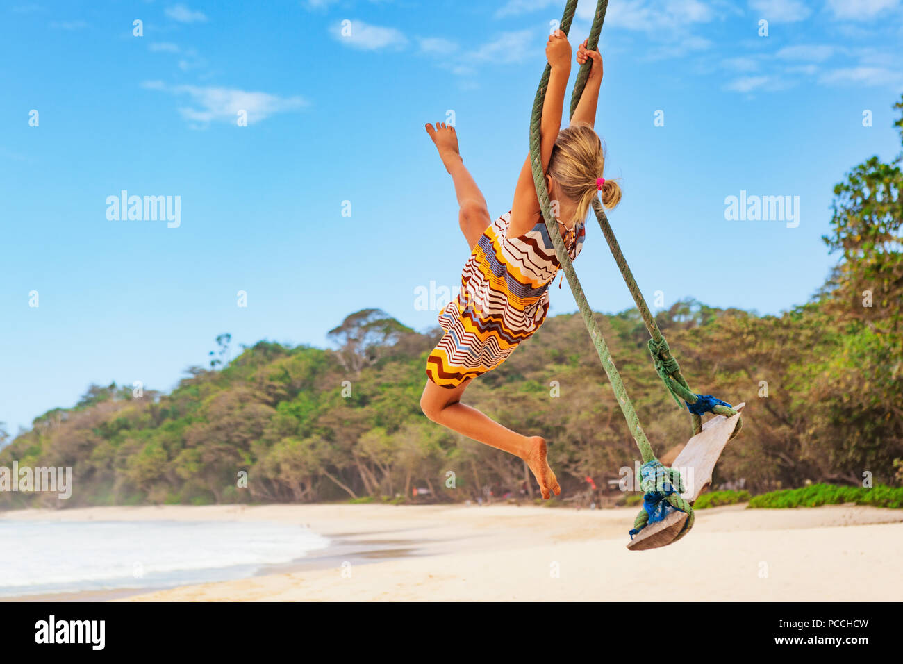 Happy girl have fun swinging high in mid air. Flying up upside down on rope swing on sea beach. Travel adventure on paradise tropical island. Family l - Stock Image