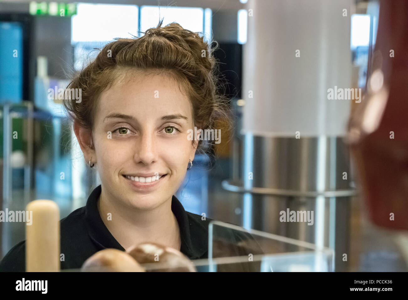 Frankfurt, Germany - July 3th, 2018: A young german woman working at a bakery inside the Frankfurt Airport. - Stock Image